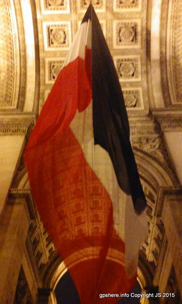 The flag of France flying underneath the Arc de Triomphe.
