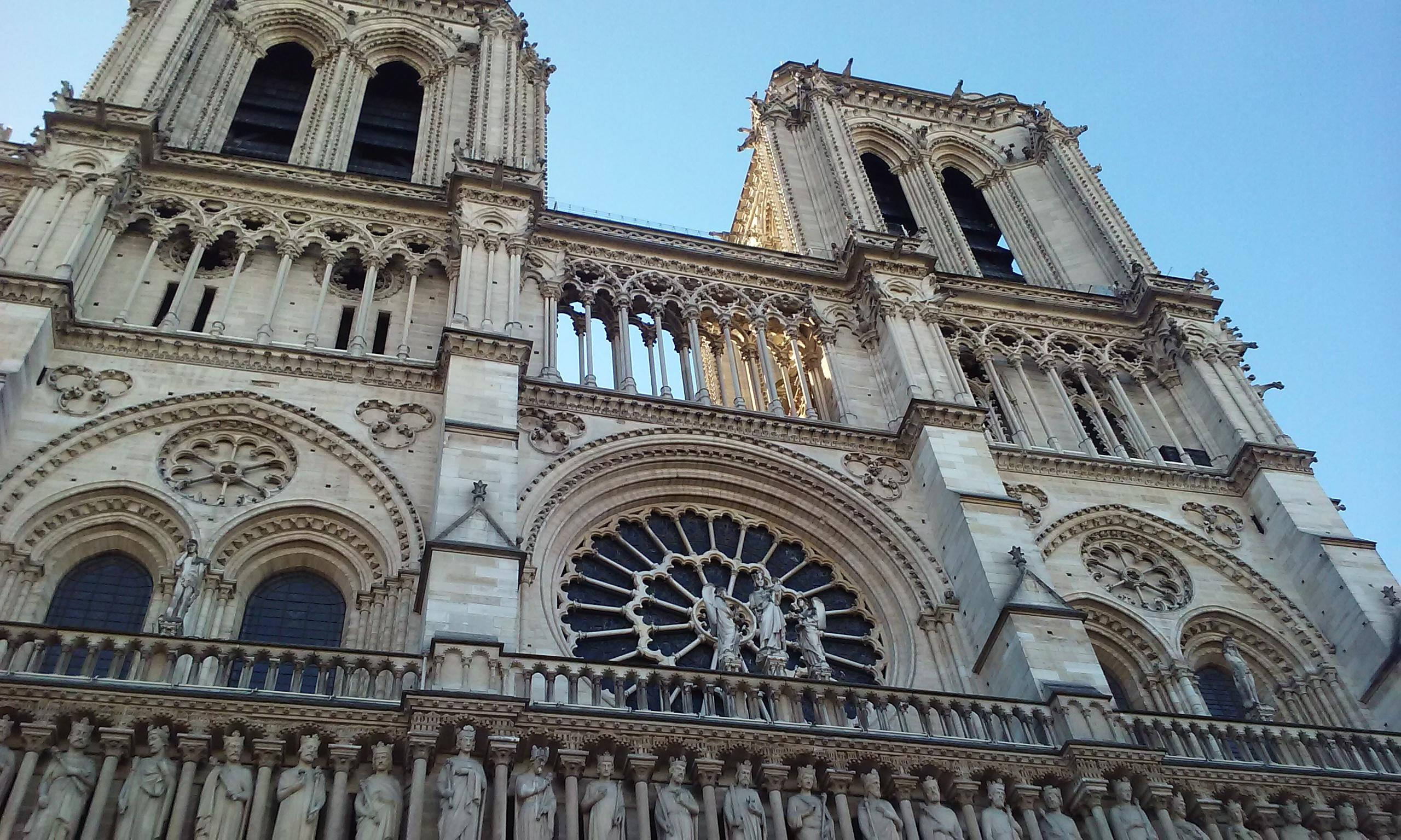 Notre Dame during the day. The intricate work above the front entrance.